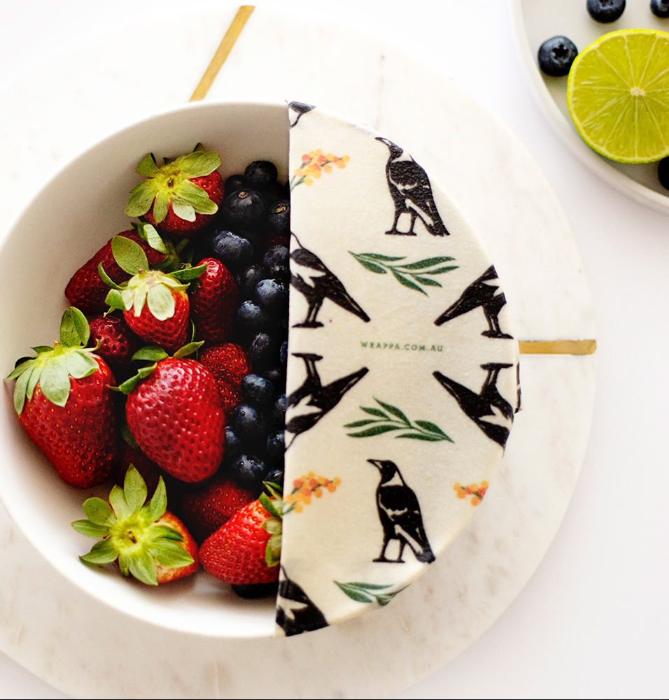 Reusable food wrap covering bowl of mixed fruit